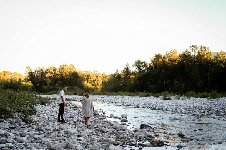 engaged couple walking along a creek in dewdney