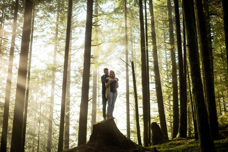 engaged couple standing on a tree stump