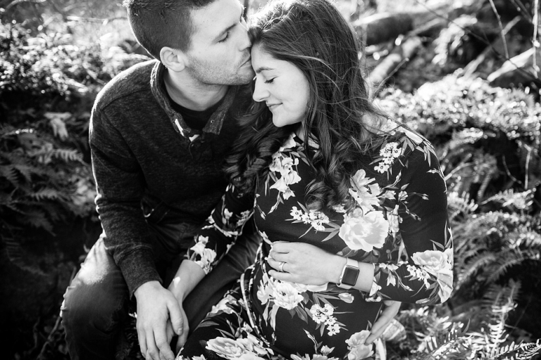 black and white photo husband kissing pregnant wife