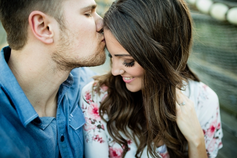 guy kissing girls forehead during engagement session
